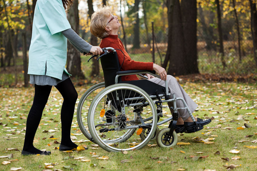 Disabled senior woman with young nurse walking at park
